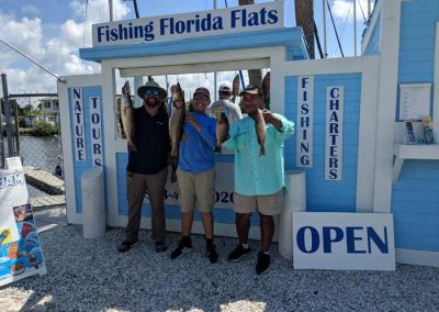 Fishing_Tourists_Holding_Ocean_Fish_Snook_Red_drum
