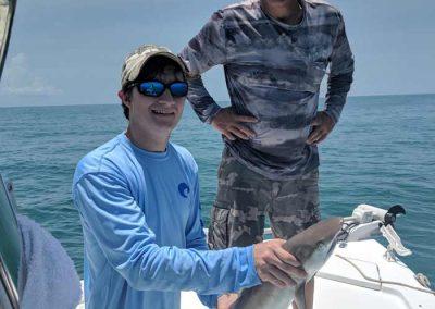 Jimmys_fishing_Charter_customer_Holding_Shark